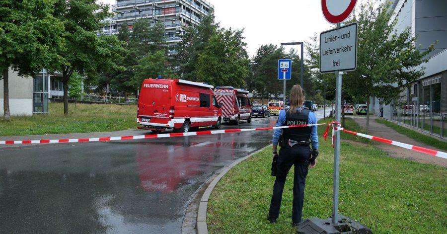 Eine Beamtin und Einsatzfahrzeuge der Feuerwehr auf dem Campus der TU Darmstadt.