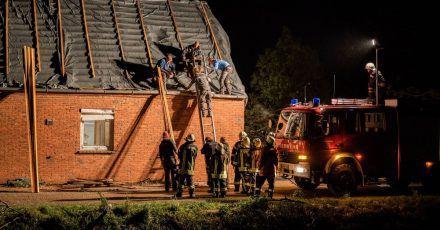 Feuerwehrleute und Helfer reparieren das Dach eines beschädigten Hauses in Berumerfehn.