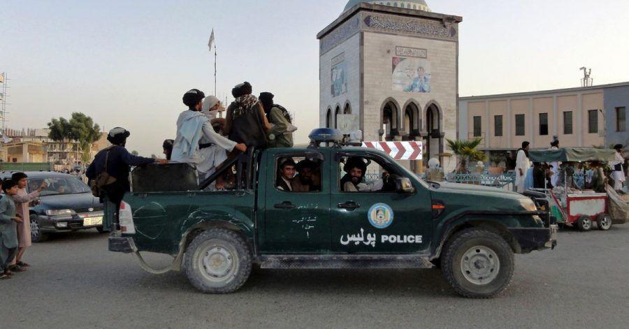 Taliban-Kämpfer patrouillieren in einem Polizeifahrzeug in Kandahar.