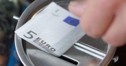 Ein Fünf-Euro-Schein wird in eine Spendendose gesteckt. Symbolbild