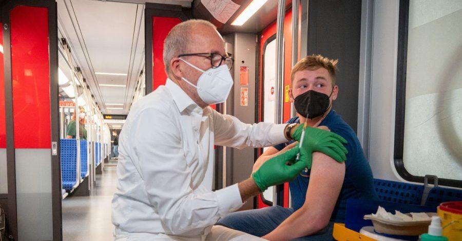 Christian Gravert, Chefmediziner der Deutschen Bahn, verabreicht einem Mann in einer Berliner S-Bahn den Impfstoff des Herstellers Johnson & Johnson.
