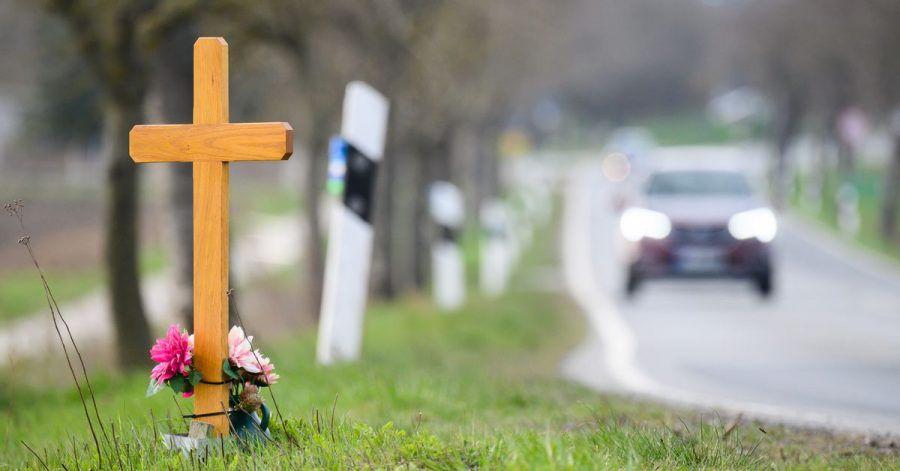 Ein Kreuz zum Gedenken an ein Opfer eines Verkehrsunfalls steht an einer Landstraße.