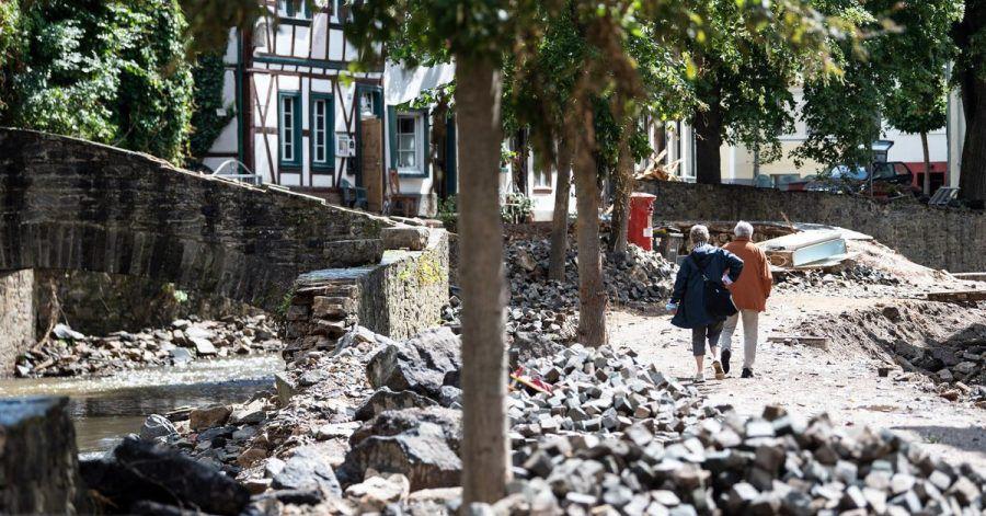 Passanten gehen durch die von der Flut zerstörte Innenstadt von Bad Münstereifel.