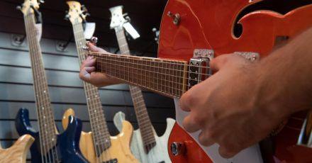 Ein Mann spielt in einem Gitarrenladen auf einer Linkshänder-Guitarre.