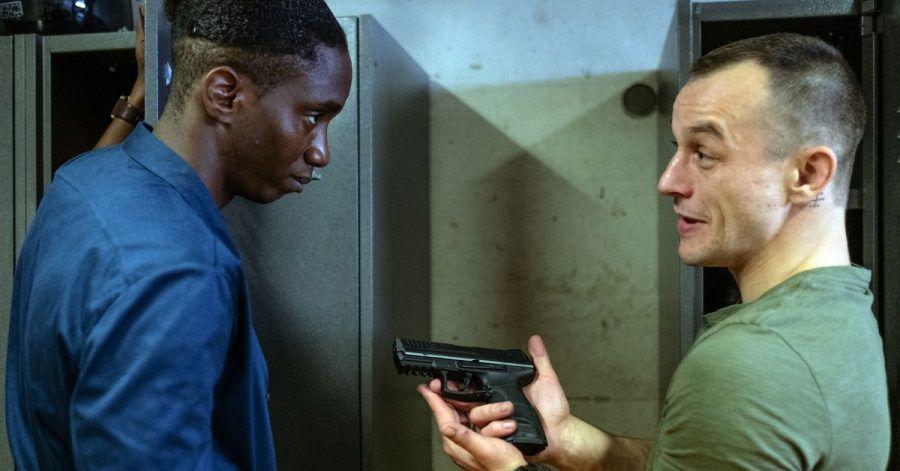 Mario (Paul Wollin, r) prahlt vor seinem Kollegen Man (Emmanuel Ajayi) mit seiner Pistole.