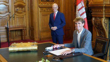 Alexander Zverev (vorne) trägt sich in das Goldene Buch der Stadt Hamburg ein (wue/spot)