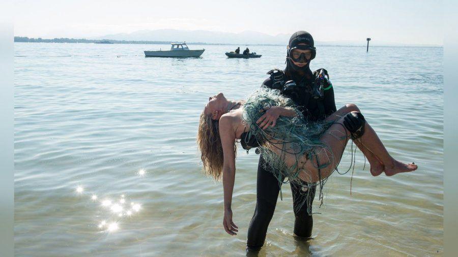 """""""Die Toten vom Bodensee - Stille Wasser"""": Ein Taucher trägt die mit Fischernetzen umspannte Leiche ans Ufer. (cg/spot)"""