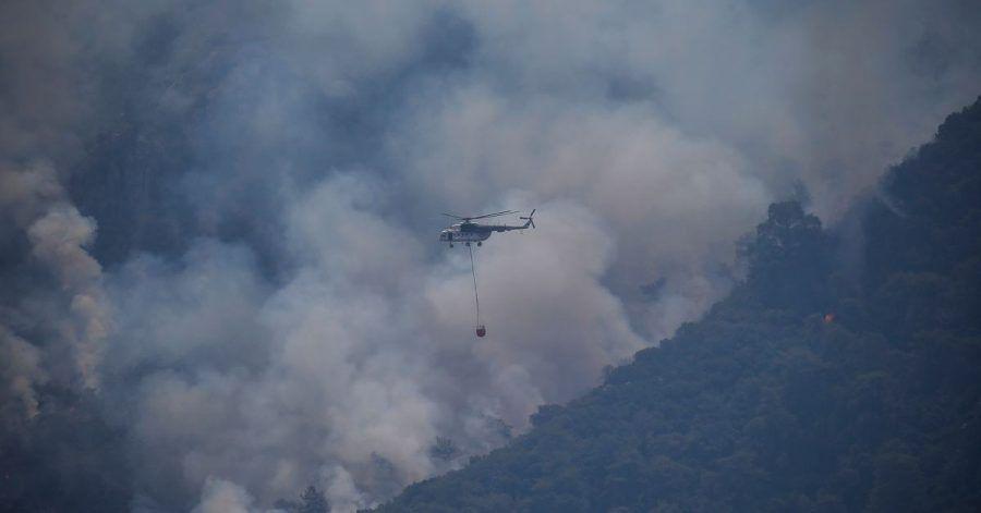 Ein Hubschrauber transportiert Löschwasser, um einen Waldbrand in der Türkei zu löschen.