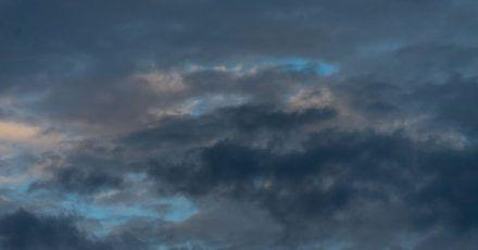 Dunkle Wolken zeichnen sich am Himmel nach Sonnenaufgang ab.