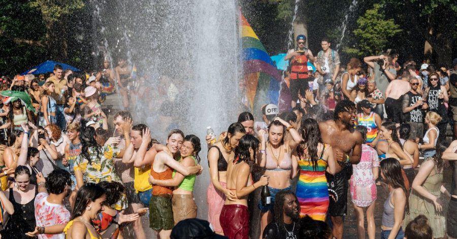 Junge Leute feiern während der Pride Parade im kühlen Nass des Brunnens am Washington Square Park in Manhattan.