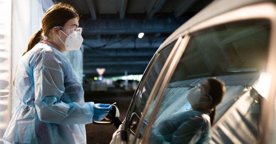 Eine Helferin testet Insassen eines Autos im «Testzentrum am Zoo» in Hannover.