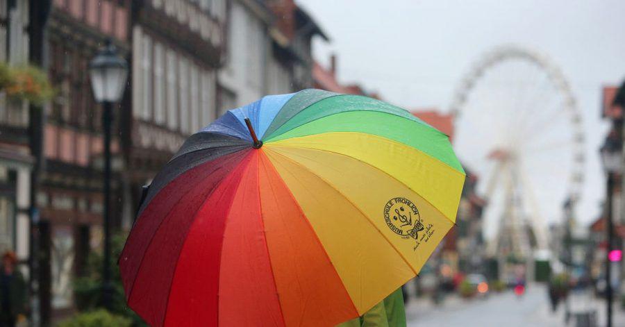 Passanten gehen bei Regenwetter durch die Fußgängerzone von Wernigerode in Sachsen-Anhalt.