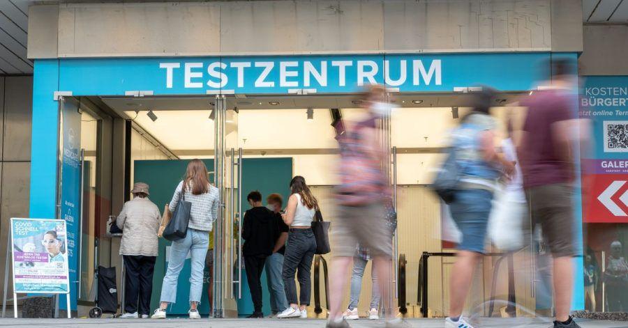 Passanten gehen an einem Corona-Testzentrum in der Fußgängerzone der Münchner Innenstadt vorbei.