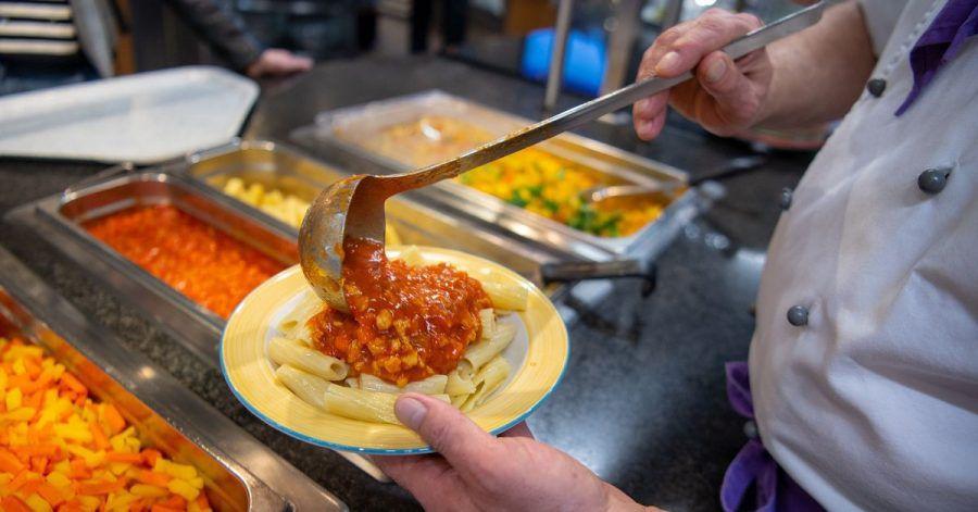 Ein Koch serviert in der veganen Mensa auf dem Campus der Technischen Universität in Berlin ein veganes Gericht.