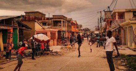 Anwohner stehen bei Sonnenuntergang auf einer Straße in Les Cayes, Haiti.