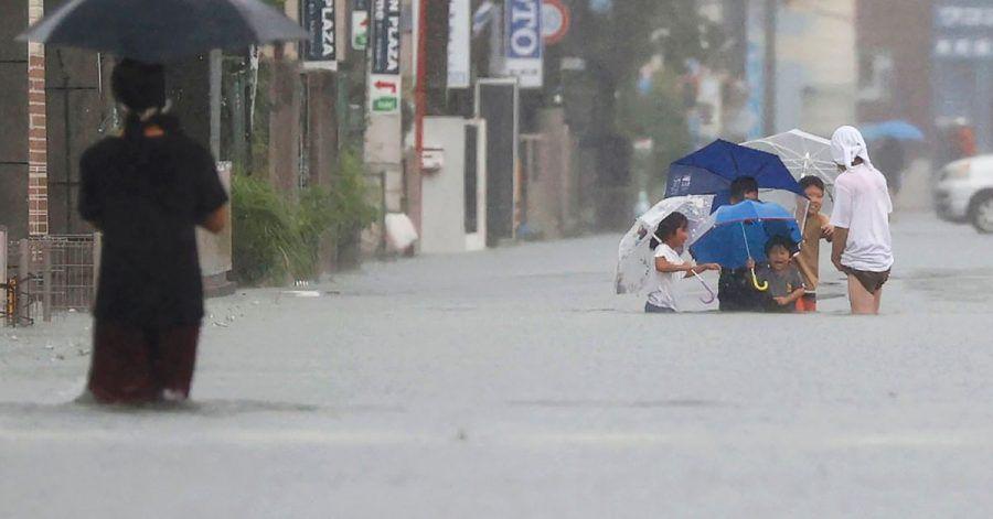 Menschen waten durch eine von starkem Regen überflutete Straße in Kurume, Präfektur Fukuoka, Westjapan.