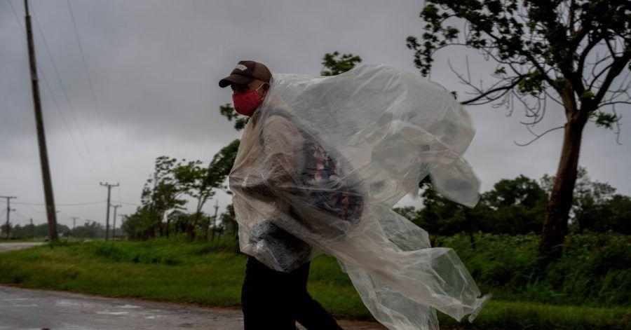 Ein Mann geht auf einer Straße nach Batabano in der kubanischen Provinz Mayabeque. Er versucht sich mit Plastikplanen gegen den von Hurrikan Ida verursachten Regen zu schützen.