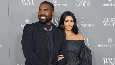 Kim Kardashian steht im Hochzeitskleid vor Kanye West
