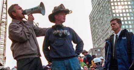 US-Präsident George W. Bush spricht in den Trümmern des New Yorker World Trade Centers neben dem pensionierten New Yorker Feuerwehrmann Bob Beckwith zu den freiwilligen Helfern und Feuerwehrleuten durch ein Megafon.