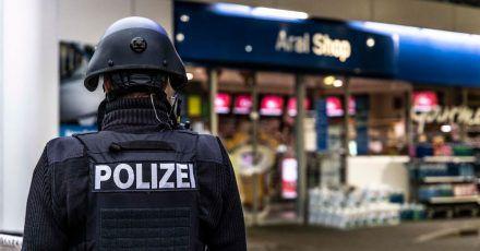 Ein Polizist steht vor der Tankstelle, an der ein Angestellter von einem Mann erschossen worden ist.