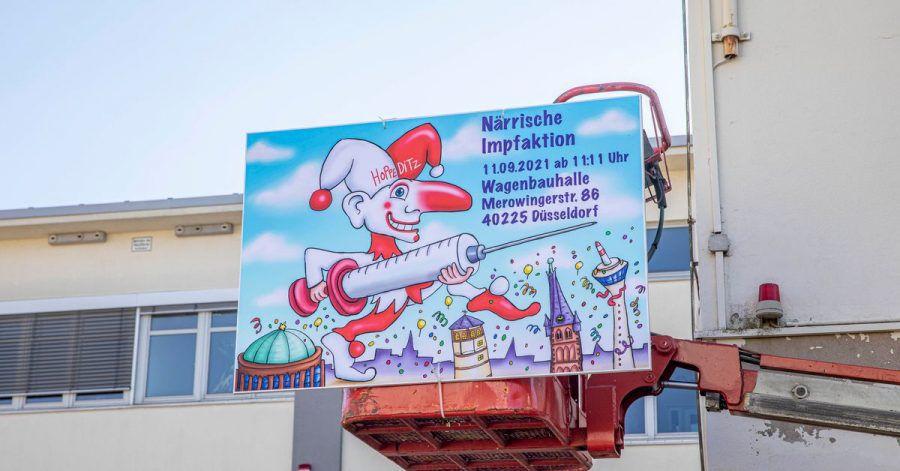 """""""Närrische Impfaktion"""" steht auf einem Schild an der Wagenbauhalle in Düsseldorf."""