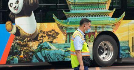 Ein Verkehrspolizist steht bei Probefahrten neben einem Bus, auf dem für den Vergnügungspark von Universal Studios geworben wird.