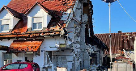 Nach der Explosion eines Wohnhauses ist das Nachbarhaus von Beschädigungen schwer gezeichnet.