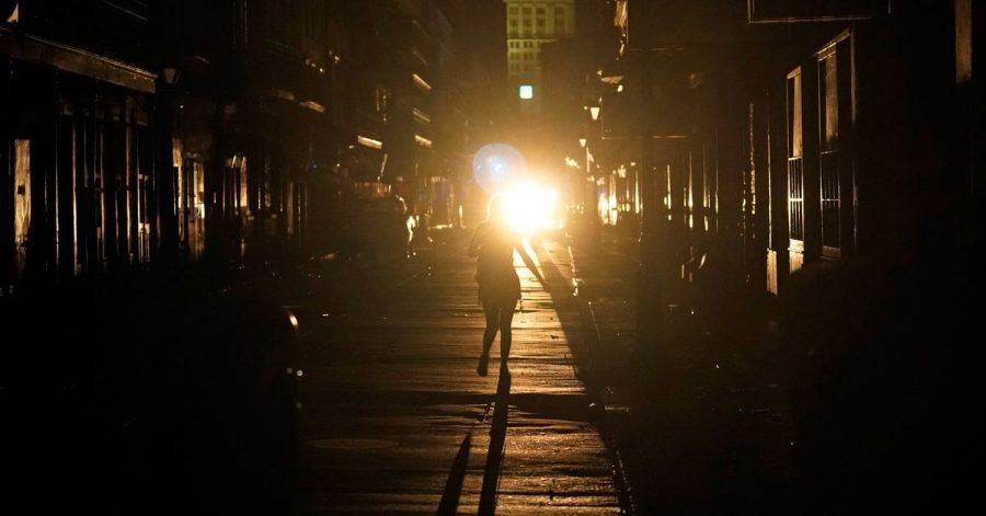 Eine Frau geht im Scheinwerferlicht eines patrouillierenden Polizeiwagens über die Bourbon Street in New Orleans.