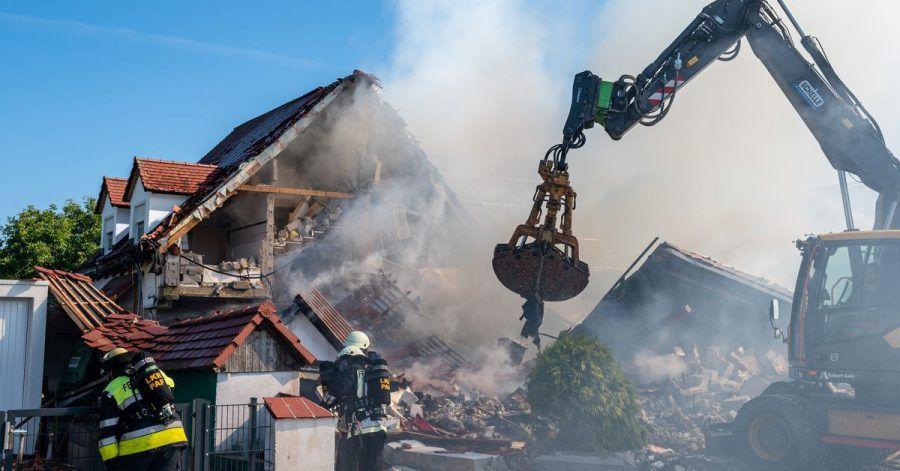 Ein Bagger räumt Teile des eingestürzten Hauses weg.