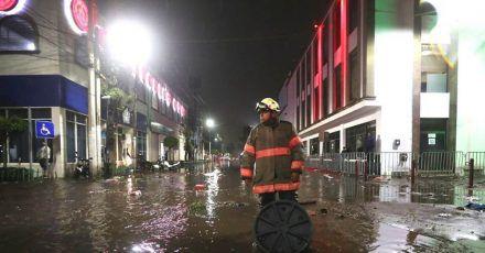 Ein Feuerwehrmann steht in einer überfluteten Straße in Ecatepec.