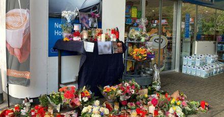 Menschen haben Blumen und Kerzen am Tatort abgelegt.