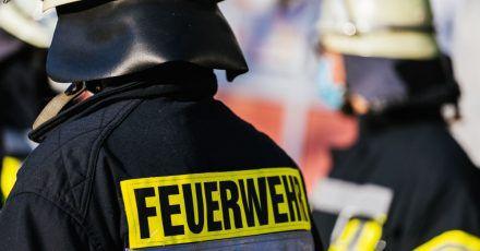 Einsatzkräfte der Feuerwehr stehen nebeneinander.