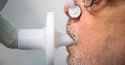 Ein Patient sitzt zur Überprüfung seiner Lungenfunktion in einem Bodyplethysmographen. Nach einer Covid-19-Erkrankung müssen viele Menschen mühsam wieder ins Leben finden.