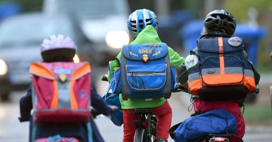 Kinder sind auf einer Straße mit dem Fahrrad unterwegs zur Schule. Symbolbild