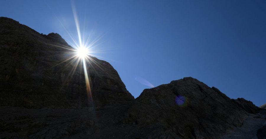 Die Sonne kommt am Morgen hinter einem Felsen im Watzmannkar (Bayern) hervor.