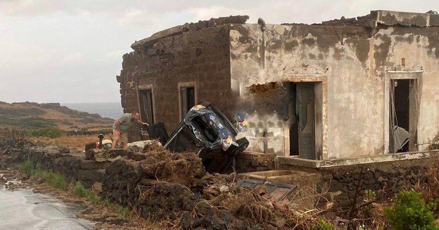 Ein zerstörtes Fahrzeug liegt abseits der Straße an einem Haus. Auf der italienischen Mittelmeerinsel Pantelleria sind zwei Menschen bei einem Unwetter ums Leben gekommen.