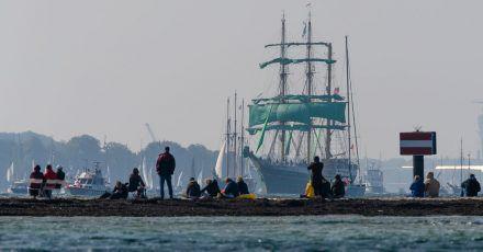 Zuschauer beobachten am Falkensteiner Strand die Windjammerparade der Kieler Woche.