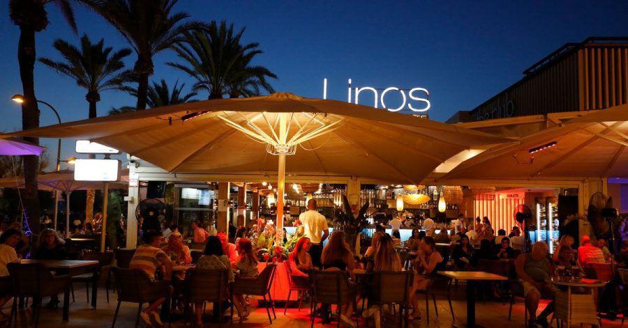 Menschen sitzen in einer Bar an der Strandpromenade von Palma.