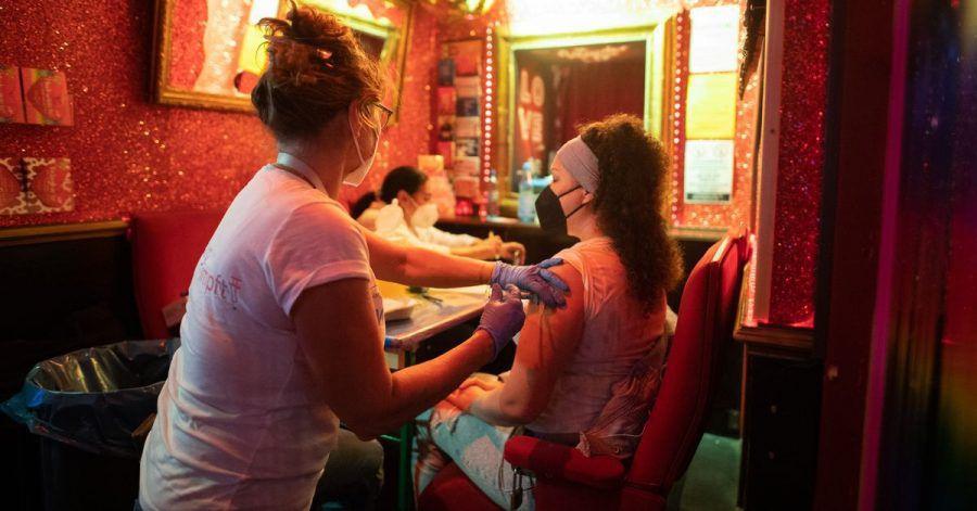 Eine junge Frau lässt sich in einer Bar nahe der Reeperbahn im Stadtteil St. Pauli gegen das Coronavirus impfen.