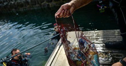 Ein Taucher hält ein Netz mit Abfällen, die er im baskischen Dorf Bermeo aus dem Meer entzogen hat. (Archivbild)