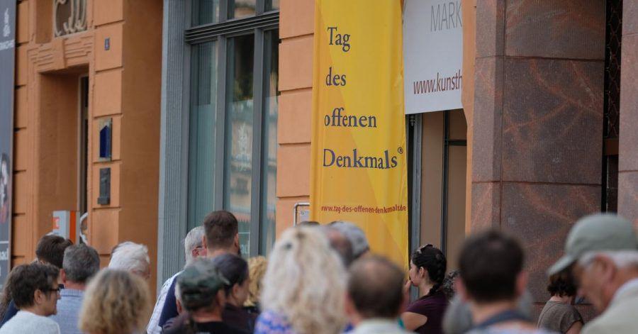 Besucher stehen vor einem historischen Gebäude in Wittenberg Schlange.