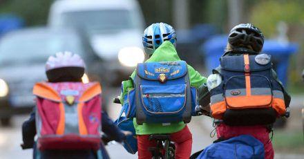 Kinder sind auf einer Straße mit dem Fahrrad unterwegs zur Schule. (Archivbild)