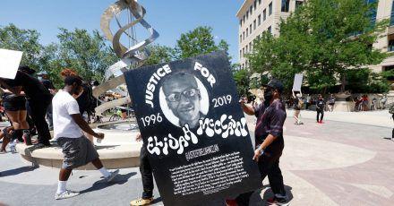 Demonstranten tragen während einer Kundgebung vor dem Polizeirevier wegen des Todes von Elijah McClain ein Plakat mit dessen Bild.