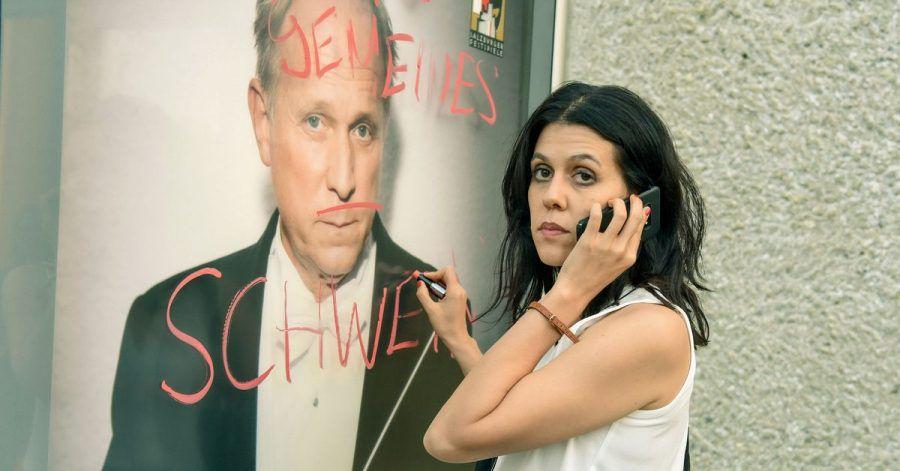Ada (Daniela Golposhin) «verziert» ein Festspielplakat mit ihrem Kommentar zum Stardirigenten Marius Atterson (Ulrich Tukur).