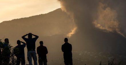 Anwohner blicken von einem Hügel aus auf die Lava, die weiterhin aus dem  Vulkan auf der Insel La Palma fließt.