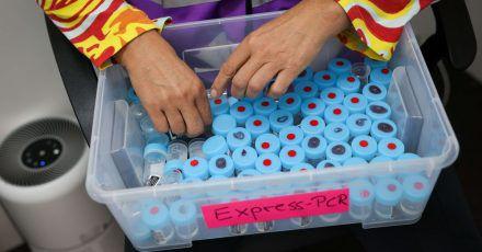 Eine Mitarbeiterin sortiert noch unbenutzte Behälter für einen PCR-Gurgeltest in einem Testcenter für Corona-Schnelltests (Antigentest) und Corona-PCR-Tests.