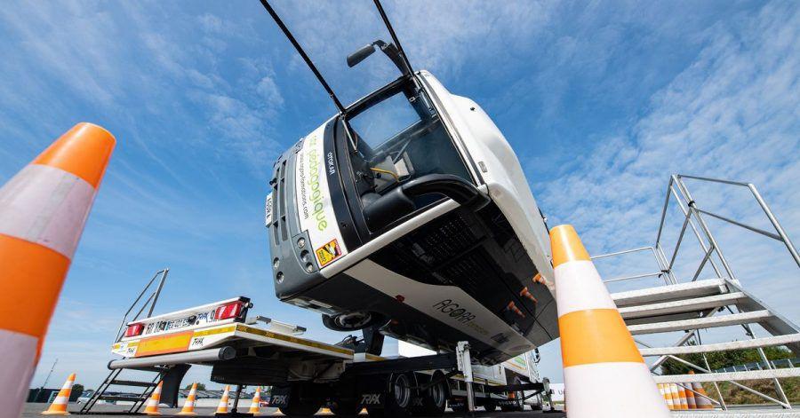Bei dem Versuchsaufbau auf dem Crashtestgelände kippt ein kleiner mit Insassen besetzter Reisebus per Hydraulik um 90 Grad auf die Seite.