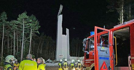 Feuerwehrleute und Polizisten stehen vor den Resten des Turms einer Windenergieanlage. Das fast 240 Meter hohe Windrad ist in sich zusammengestürzt.