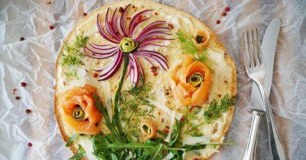 Kreativer Pizza-Belag: Mit roten Zwiebelstreifen, Rucola und Dill sowie  Lachs- und Zucchini-Röschen entsteht im Handumdrehen eine Blumenwiese zum Essen.
