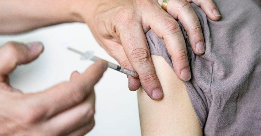 Ein Kinder- und Jugendarzt in Berlin impft eine junge Frau mit dem Corona-Impfstoff Comirnaty von Biontech/Pfizer.